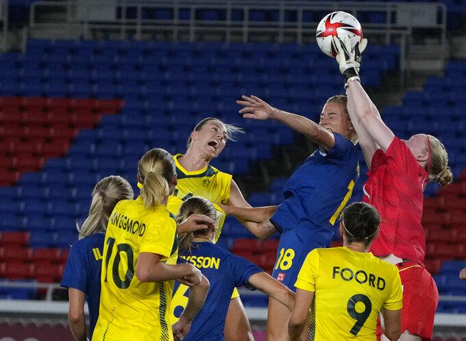 Sweden's goalkeeper Hedvig Lindahl, right, cuts off a corner kick during a women's semifinal soccer match against Australia at the 2020 Summer Olympics, Monday, Aug. 2, 2021, in Yokohama, Japan. (AP Photo/Kiichiro Sato)