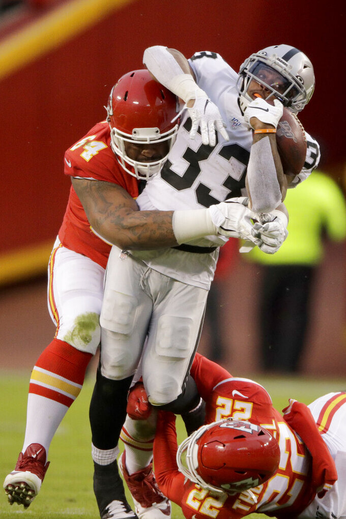 Oakland Raiders running back DeAndré Washington (33) is tackled by Kansas City Chiefs defensive tackle Mike Pennel (64) and safety Juan Thornhill (22) during the first half of an NFL football game in Kansas City, Mo., Sunday, Dec. 1, 2019. (AP Photo/Charlie Riedel)