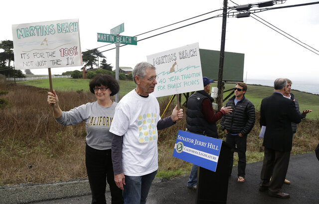 FILE - In this Feb. 10, 2014, file photo, Julie Graves, left, of Albany, Calif., and Chris Adams, second from left, of Berkeley, Calif., hold up signs in support of a beach access bill near Martin's Beach in Half Moon Bay, Calif. California officials are suing a billionaire who has been fighting for more than a decade to keep a secluded beach to himself, a move designed to ensure that the public always has access the scenic stretch of sand. The lawsuit was filed Monday, Jan. 6, 2020, on behalf of the California State Lands Commission and Coastal Commission. (AP Photo/Eric Risberg, File)