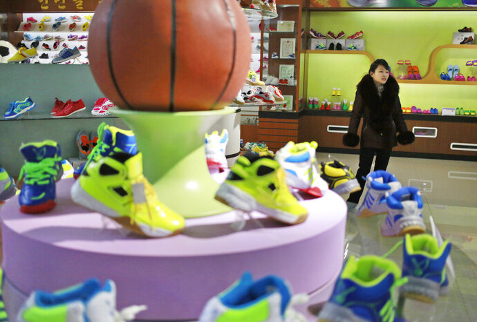 In this Friday, Feb. 1, 2019, photo, a guide stands near a basketball shoe display in a product exhibition room at the Ryuwon Shoe Factory that specializes in sports footwear, in Pyongyang, North Korea. North Korean pop culture, long dismissed by critics as a kitschy throwback to the dark days of Stalinism, is getting a major upgrade under leader Kim Jong Un. The changes are being seen in everything from television dramas and animation programs to the variety and packaging of consumer goods, which have improved significantly under Kim. (AP Photo/Dita Alangkara)