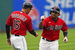 Cleveland Indians' Jose Ramirez, right, is congratulated by third base coach Mike Sarbaugh after Ramirez hit a solo home run in the first inning in the first baseball game of a doubleheader against the Detroit Tigers, Wednesday, June 30, 2021, in Cleveland. (AP Photo/Tony Dejak)