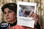 Attorney Gloria Allred, holds a picture of Jeffrey Epstein and her client Teala Davis during a news conference, Thursday, Nov. 21, 2019, in New York, about the filing of a lawsuit against the estate of Epstein. Davies says she was 17 when she was victimized by Epstein. (AP Photo/Jeenah Moon)