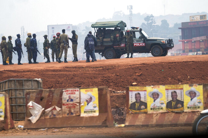 """FILE - In this Thursday, Jan. 14, 2021 file photo, security forces gather on election day in Kampala, Uganda. The United States said Friday, April 16, 2021 that it is imposing visa restrictions on """"those believed to be responsible for, or complicit in, undermining the democratic process in Uganda,"""" including during the election in January and the campaign period. (AP Photo/Jerome Delay, File)"""