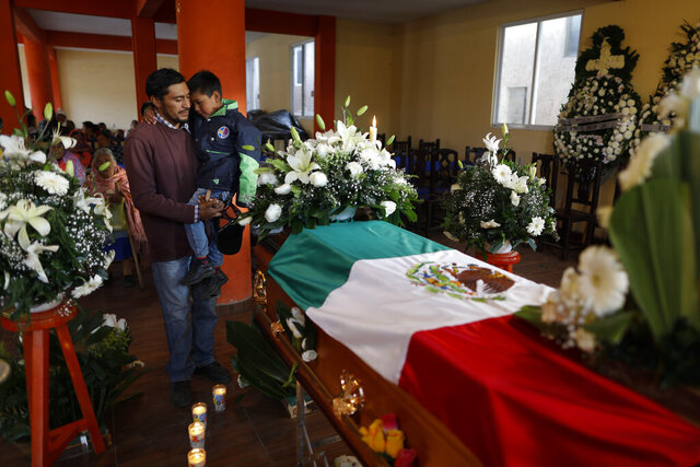 Mourners pay their respects next to the coffin of environmental activist Homero Gomez Gonzalez at his wake in Ocampo, Michoacan state, Mexico, Thursday, Jan. 30, 2020. Relatives of the anti-logging activist who fought to protect the winter habitat of monarch butterflies don't know whether he was murdered or died accidentally, but they say they do know one thing for sure: something bad is happening to rights and environmental activists in Mexico, and people are afraid.(AP Photo/Rebecca Blackwell)