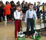 In this Sunday, Feb. 17, 2019 photo, Terelle Gaston, 7, left, and his brother Tawann Gaston, Jr., 8, wait to sweep up after haircuts during