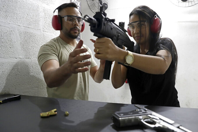 Gisely Nunes learns to handle a submachine gun from an instructor at the Valparaiso Shooting Club on the outskirts of Brasilia, Brazil, Saturday, March 6, 2021. Newly-issued gun decrees, which have worried public security analysts, are to take effect by mid-April unless the Brazilian congress or courts intervene. (AP Photo/Eraldo Peres)