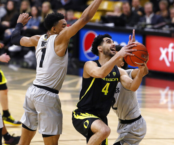 Oregon guard Ehab Amin, center, drives to the rim between Colorado guards Tyler Bey, left, and Daylen Kountz in the first half of an NCAA college basketball game Saturday, Feb. 2, 2019, in Boulder, Colo. (AP Photo/David Zalubowski)