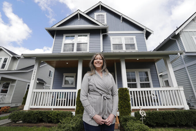 In this Wednesday, April 1, 2020 photo, Rebeka McBride stands in front of her home that is in the process of being sold in Monroe, Wash., outside of Seattle. She put her house on the market in early March and is in the process of closing on the sale. But with the U.S. economy now collapsing, the family is less confident about their move to a Minneapolis suburb, where McBride sees brighter job prospects in her field of medical device research.(AP Photo/Elaine Thompson)