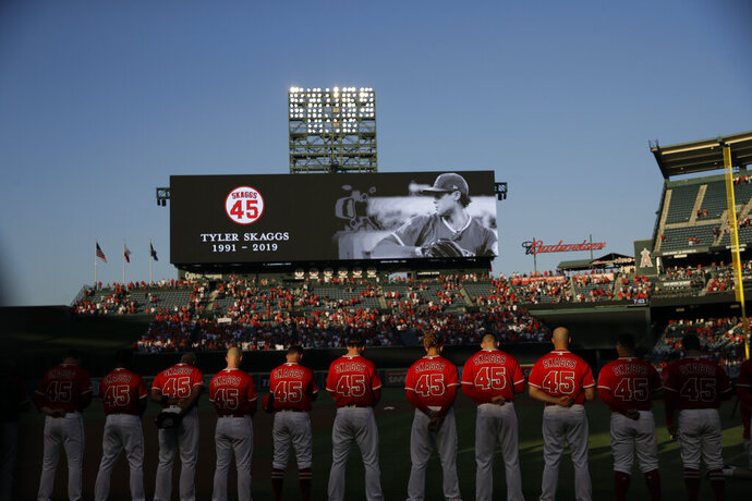 Members of the Los Angeles Angels observe a moment of silence for teammate Tyler Skaggs, before a baseball game against the Seattle Mariners on Friday, July 12, 2019, in Anaheim, Calif. (AP Photo/Marcio Jose Sanchez)