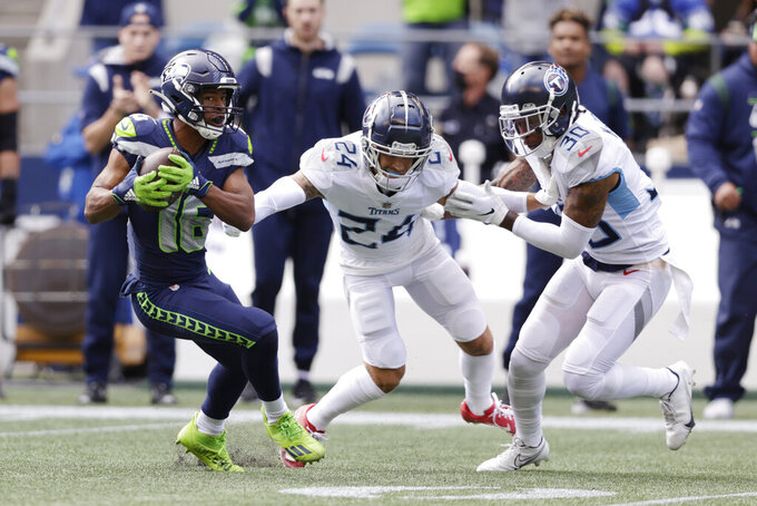 Seattle Seahawks' Tyler Lockett, left, breaks from the grasp of Tennessee Titans cornerback Elijah Molden (24) to run for a touchdown after a reception as strong safety Bradley McDougald (30) looks on during the first half of an NFL football game, Sunday, Sept. 19, 2021, in Seattle. (AP Photo/John Froschauer)