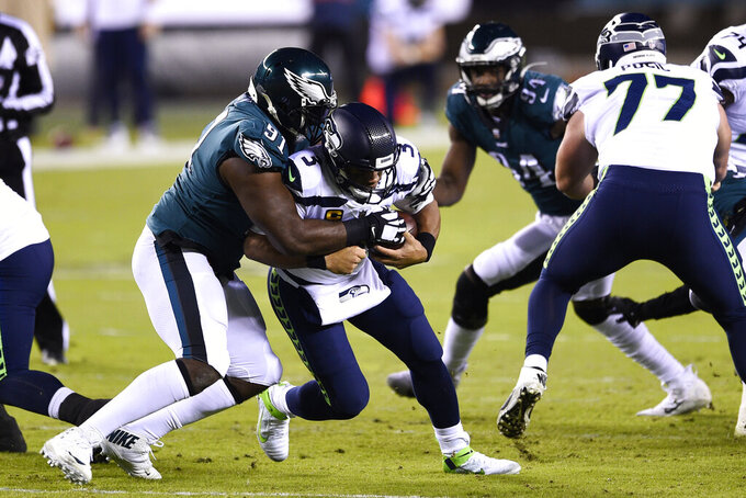 Philadelphia Eagles' Fletcher Cox (91) tackles Seattle Seahawks' Russell Wilson (3) during the first half of an NFL football game, Monday, Nov. 30, 2020, in Philadelphia. (AP Photo/Derik Hamilton)
