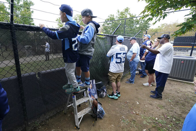 Quinn Keefer, 9, left, of Denver, shares a ladder with Jesse Winger, 14, as they try to get autographs as Tennessee Titans players arrive at Nissan Stadium before an NFL football game between the Titans and the Kansas City Chiefs Sunday, Oct. 24, 2021, in Nashville, Tenn. (AP Photo/Mark Humphrey)