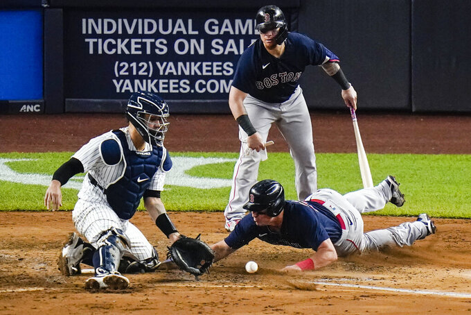 Boston Red Sox's Christian Vazquez, top right, watches as Hunter Renfroe, bottom right, slides past New York Yankees catcher Gary Sanchez, left, to score on a double by Red Sox's Marwin Gonzalez during the sixth inning of a baseball game Friday, June 4, 2021, in New York. (AP Photo/Frank Franklin II)