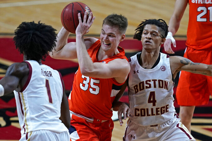 Syracuse guard Buddy Boeheim (35) drives with the ball between the defense of Boston College forward CJ Felder (1) and guard Makai Ashton-Langford (4) during the first half of an NCAA college basketball game, Saturday, Dec. 12, 2020, in Boston. (AP Photo/Elise Amendola)