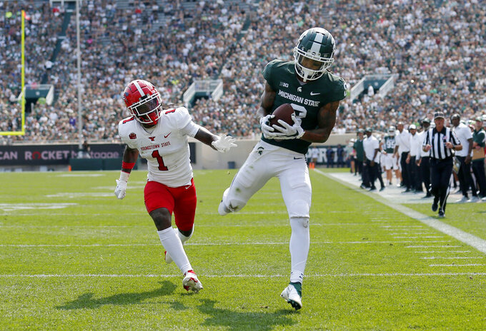 Michigan State receiver Jalen Nailor, right, catches a pass for a touchdown against Youngstown State's Zaire Jones (1) during the third quarter of an NCAA college football game, Saturday, Sept. 11, 2021, in East Lansing, Mich. Michigan State won 42-14. (AP Photo/Al Goldis)