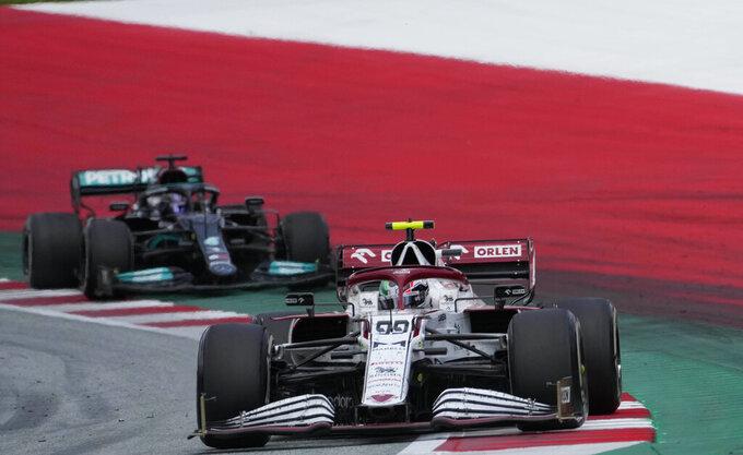 Alfa Romeo driver Antonio Giovinazzi of Italy drives ahead of Mercedes driver Lewis Hamilton of Britain during the Styrian Formula One Grand Prix at the Red Bull Ring racetrack in Spielberg, Austria, Sunday, June 27, 2021. (AP Photo/Darko Vojinovic)