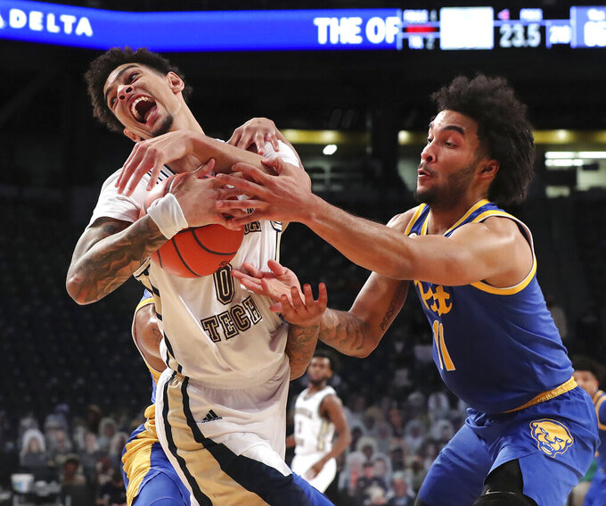 Georgia Tech guard Michael Devoe, left, holds onto a rebound against Pittsburgh defender Justin Champagnie in the final minutes of an NCAA college basketball game in Atlanta, Sunday, Feb 14, 2021. Georgia Tech beat Pittsburgh 71-65. (Curtis Compton/Atlanta Journal-Constitution via AP)