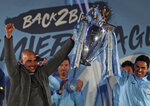 Manchester City coach Pep Guardiola, left, and his assistant Mikel Arteta hold the trophy as they celebrate with their supporters at the Etihad Stadium in Manchester, England, Sunday May 12, 2019 the day they won the English Premier League title. Manchester City retained the Premier League trophy after coming from behind to beat Brighton 4-1 and see off Liverpool's relentless challenge on the final day of the season on Sunday. (AP Photo/Jon Super)