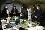 French President Emmanuel Macron, right, wears a face mask as he visits the military field hospital in Mulhouse, eastern France, Wednesday, March 25, 2020. French President Emmanuel Macron launched a special military operation Wednesday to help fight the new virus in one of the world's hardest-hit countries. The new coronavirus causes mild or moderate symptoms for most people, but for some, especially older adults and people with existing health problems, it can cause more severe illness or death. (Mathieu Cugnot/Pool via AP)