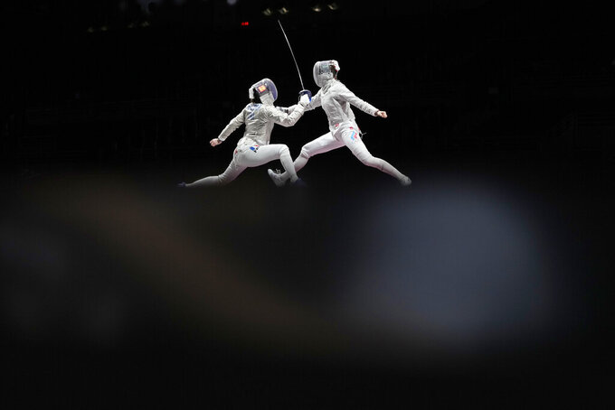 Cecilia Berder of France, left, and Sofia Pozdniakova of the Russian Olympic Committee compete in the women's Sabre team final competition at the 2020 Summer Olympics, Saturday, July 31, 2021, in Chiba, Japan. (AP Photo/Hassan Ammar)