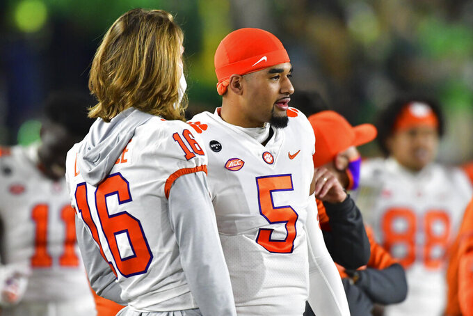 Clemson quarterback Trevor Lawrence (16) talks to quarterback D.J. Uiagalelei (5) during the first quarter of the team's NCAA college football game against Notre Dame on Saturday, Nov. 7, 2020, in South Bend, Ind. (Matt Cashore/Pool Photo via AP)