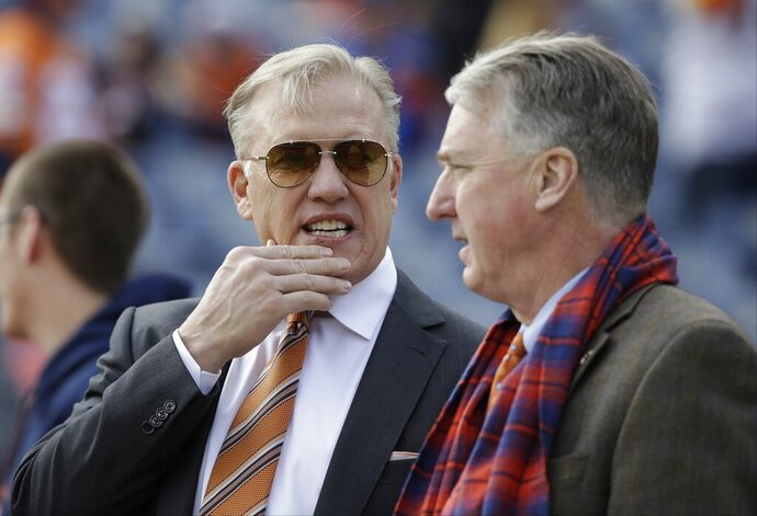 FILE - In this Sunday, Jan. 1, 2017 file photo, Denver Broncos general manager John Elway, left, stands with Broncos President and CEO Joe Ellis, right, before an NFL football game against the Oakland Raiders in Denver. The Denver Broncos' new general manager will join an organization embroiled in a family ownership feud and will work in the shadow of John Elway, whom team president Joe Ellis described as