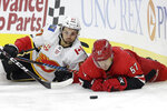 Carolina Hurricanes defenseman Trevor van Riemsdyk (57) and Calgary Flames right wing Michael Frolik (67) fall to the ice while chasing the puck during the first period of an NHL hockey game in Raleigh, N.C., Tuesday, Oct. 29, 2019. (AP Photo/Gerry Broome)