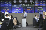 A currency trader walks by screens showing foreign exchange rates at the foreign exchange dealing room of the KEB Hana Bank headquarters in Seoul, South Korea, Thursday, Sept. 24, 2020. Asian shares were mostly lower Thursday as caution again after a retreat on Wall Street driven by a decline in technology shares. (AP Photo/Ahn Young-joon)