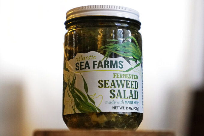 A jar of Atlantic Sea Farms seaweed salad is seen Thursday, Dec. 10, 2020, in Freeport, Maine. Like many pieces of the seafood industry, seaweed is highly dependent on the restaurant sector, which made the pandemic a potentially major setback. But representatives for a company that works with two dozen Maine seaweed farmers said it nearly doubled its harvest this year to 450,000 pounds.  (AP Photo/Robert F. Bukaty)