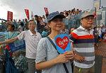 A woman holds a fan reads