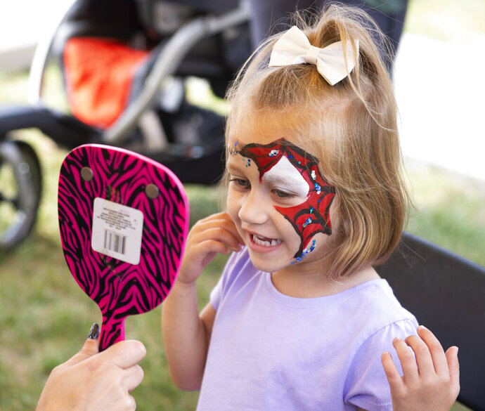 In this Saturday, Sept. 7, 2019 photo, Charlie Winter checks out her new face paint in a mirror during Applefest at Christ United Methodist in Lincoln, Neb. (Emily Janey/Lincoln Journal Star via AP)