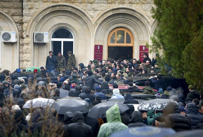 Protesters besiege the offices of Abkhazia President Raul Khadzhimba in the city of Sukhumi, in Georgia's breakaway province of Abkhazia, Thursday, Jan. 9, 2020.  The demonstrators are demanding the resignation of Raul Khadzhimba, who was re-elected Abkhazia's president in September 2019, and some demonstrators scuffled with guards as they tried to break into the presidential administration building. (AP Photo)