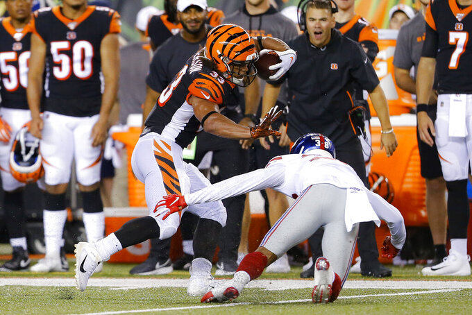Cincinnati Bengals running back Rodney Anderson (33) tries to avoid New York Giants cornerback Henre' Toliver (38) during the second half of an NFL preseason football game Thursday, Aug. 22, 2019, in Cincinnati. (AP Photo/Gary Landers)