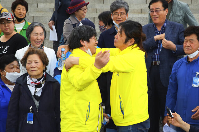 Victims of Brothers Home Choi Seung-woo and Han Jong-sun, center left, hug each other after parliament passed a law for investigating past human rights violations at the National Assembly in Seoul, South Korea, Wednesday, May 20, 2020. South Korea's parliament on Wednesday passed a law allowing new investigations into the country's past human rights atrocities, rewarding a years-long struggle for redemption by survivors of Brothers Home, a state-funded vagrants' facility where thousands were enslaved and abused in the 1970s and '80s. (Jin Sung-chul/Yonhap via AP)