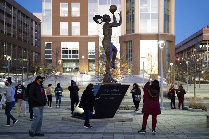 South Carolina NCAA college basketball fans look at a new statue honoring A'ja Wilson before an NCAA college basketball game against Arkansas Monday, Jan. 18, 2021, in Columbia, S.C.  Wilson, preparing for her fourth season with the Las Vegas Aces of the WNBA as the league's reigning MVP was the guest of honor at Monday's official christening of the statue of her likeness that honors her play off the court and representation of the university and athletics program away from competition.(AP Photo/Sean Rayford)