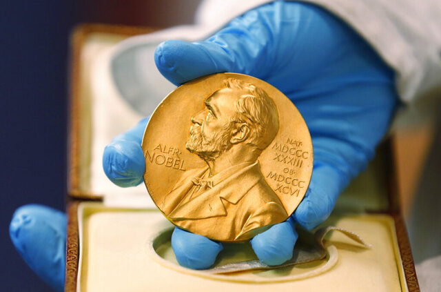 FILE - In this April 17, 2015, file photo, a national library employee shows a gold Nobel Prize medal in Bogota, Colombia. The Nobels, with new winners announced starting Monday, Oct. 5, 2020, often concentrate on unheralded, methodical, basic science. (AP Photo/Fernando Vergara, File)