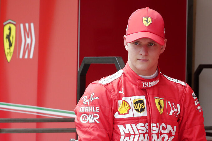 Mick Schumacher walks in the pit during his first F1 test for Ferrari at the Bahrain International Circuit in Sakhir, Bahrain, Tuesday, April 2, 2019. Mick Schumacher has moved closer to emulating his father Michael by driving a Ferrari Formula One car in an official test. Schumacher's father won seven F1 titles, five of those with Ferrari and holds the record for race wins with 91. (AP Photo/Hassan Ammar)