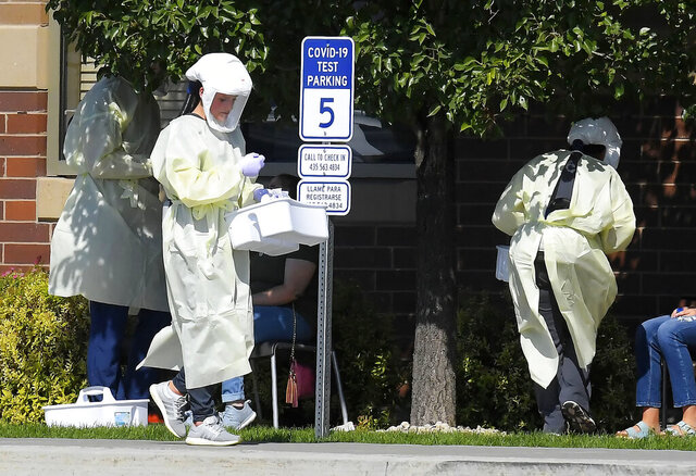Workers test Utah State University students for COVID-19 on Sunday, Aug. 30, 2020, in Hyde Park, Utah. Students from four dorms were tested and quarantined after the virus was detected in the wastewater from those buildings. (Eli Lucero/The Herald Journal via AP)