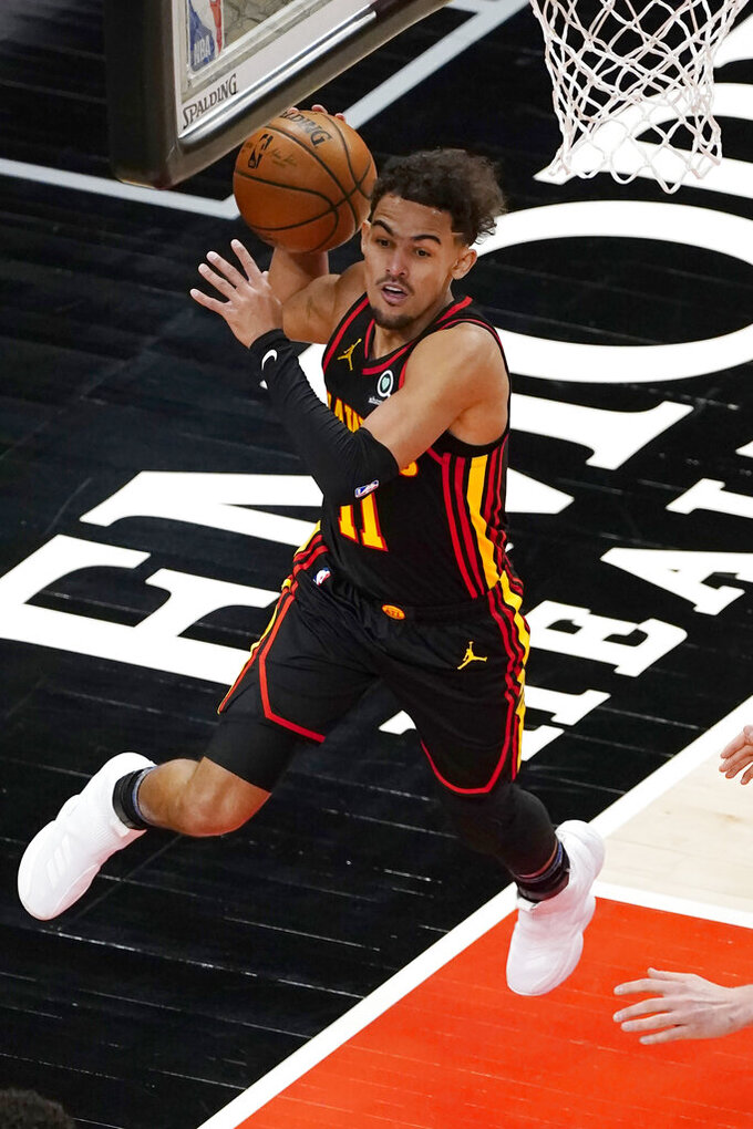 Atlanta Hawks guard Trae Young (11) keeps the ball in play during the first half of the team's NBA basketball game against the Denver Nuggets on Sunday, Feb. 21, 2021, in Atlanta. (AP Photo/John Bazemore)