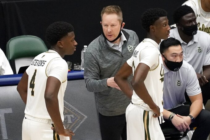 Colorado State guard Isaiah Stevens (4) and guard Kendle Moore, right, take instruction from head coach Niko Medved, center, in the second half of an NCAA college basketball game against Memphis in the semifinals of the NIT, Saturday, March 27, 2021, in Frisco, Texas. (AP Photo/Tony Gutierrez)