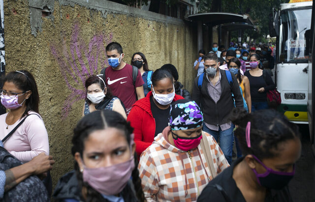 Pedestrians and commuters wearing face masks amid the new coronavirus pandemic crowd a sidewalk near a bus stop in Caracas, Venezuela, Monday, June 1, 2020. After two and a half months of COVID-19 related quarantine, some industries are allowed to reactivate under a scheme of five days' work and 10 days rest. (AP Photo/Ariana Cubillos)