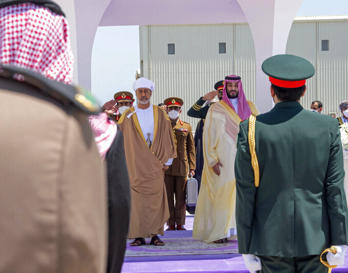 In this photo released by Saudi Royal Palace, Saudi Crown Prince Mohammed bin Salman, center right, and Omani Sultan Haitham bin Tariq, center left, review an honor guard during the welcoming ceremony at Neom Bay Airport, in the Tabuk Province of northwestern Saudi Arabia, Sunday, July 11, 2021. Sultan Haitham started the first visit by an Omani ruler in years against the backdrop of renewed diplomatic efforts to end the war in Yemen and the sultanate's worsening economic woes. (Bandar Aljaloud/Saudi Royal Palace via AP)