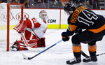 Detroit Red Wings' Jimmy Howard, left, blocks a shot by Philadelphia Flyers' Sean Couturier during the second period of an NHL hockey game, Saturday, Feb. 16, 2019, in Philadelphia. (AP Photo/Matt Slocum)