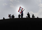 Anti-government protesters wave a Lebanese flag, as they stand on the Dome City Center known as