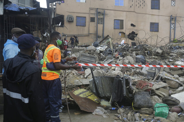 People gather at the site of a collapsed building in Lagos Nigeria, Saturday July 11, 2020. A building has collapsed in Lagos, Nigeria and scores of people have gathered at the scene. Local reports say two people are dead. (AP Photo/Sunday Alamba)
