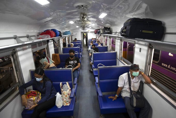 Passengers wear face masks on a train bound for northeastern province of Ubon Ratchathani, at Hua Lamphong Railway Station in Bangkok, Thailand, Friday, April 9, 2021. Thai authorities were struggling Friday to contain a growing coronavirus outbreak just days before the country's traditional Songkran New Year's holiday, when millions of people travel around the country. (AP Photo/Sakchai Lalit)