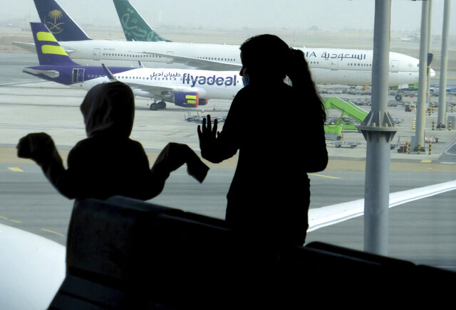 Passengers watch aircraft on the tarmac as they wait for their flight at the King Abdulaziz International Airport in Jiddah, Saudi Arabia, Tuesday, July 28, 2020. Few flights are scheduled for international departures only but the authorities have eased domestic travel restrictions since June. (AP Photo/Amr Nabil)