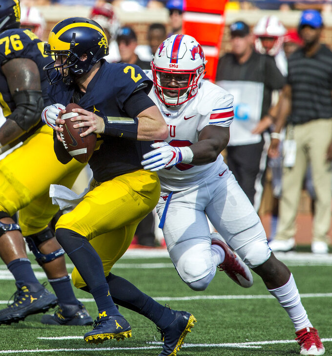 Michigan quarterback Shea Patterson (2) tries to escape a tackle from SMU defensive end Toby Ndukwe, right, in the second quarter of an NCAA college football game in Ann Arbor, Mich., Saturday, Sept. 15, 2018. (AP Photo/Tony Ding)