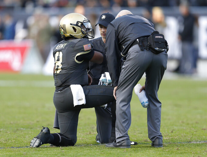 Army quarterback Kelvin Hopkins Jr. (8) is assisted by team personnel after an injury during the second half of Armed Forces Bowl NCAA college football game against Houston, Saturday, Dec. 22, 2018, in Fort Worth, Texas. (AP Photo/Jim Cowsert)