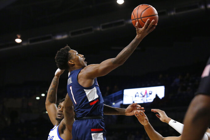 Connecticut guard Christian Vital (1) goes to the basket in front of Tulsa forward Martins Igbanu, left, during the first half of an NCAA college basketball game in Tulsa, Okla., Thursday, Feb. 6, 2020. (AP Photo/Sue Ogrocki)